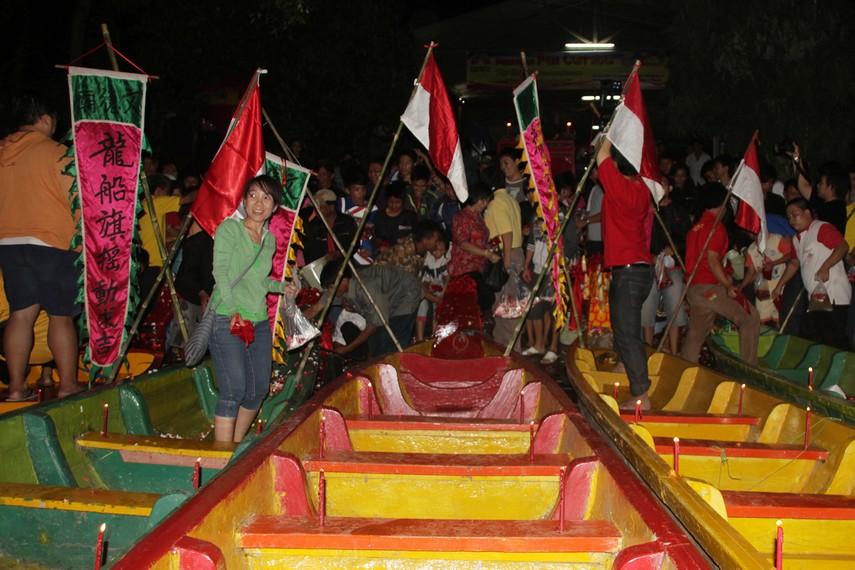 Masyarakat turut memandikan perahu naga yang keesokan harinya akan digunakan untuk lomba perahu naga