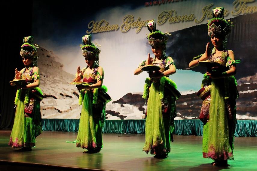 Para penari membawa saweran yang berisi beras kuning dan logam benggol