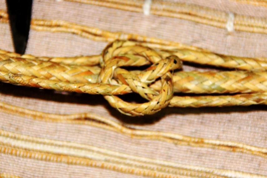 Tali pengait mandau yang menunjukkan status mandau