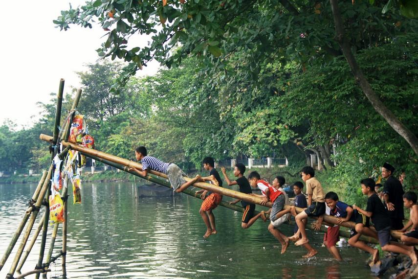 Tingkah polah anak-anak yang menjadi peserta panjat pinang Situ Sabakan selalu mengundang tawa
