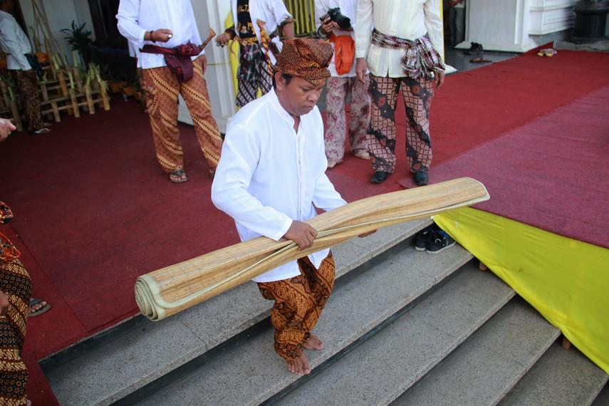 Gulungan tikar berisi beras dari tambak karang dibawa oleh petugas keraton ke tengah kerumunan masyarakat