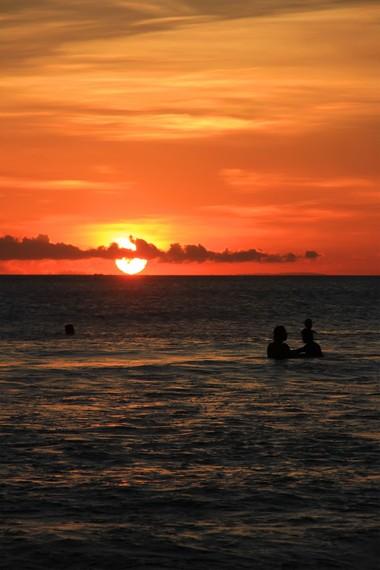 Bias jingga mentari sore turun dari langit hingga akhirnya hilang bagai ditelan lautan di Pantai Kuta