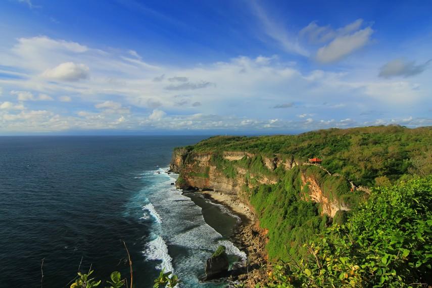 Panorama eksotis sisi sebelah utara dari Pura Uluwatu, tebing karang yang menghijau dikelilingi lautan yang biru