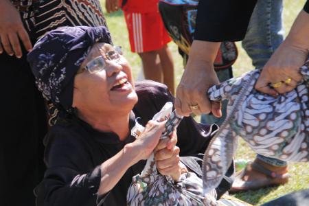 Kegembiraan masyarakat saling berebut kue dalam ritual sedekah kue dalam tradisi Seren Taun