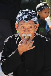 Seorang kokolot sedang memakan kue dalam ritual sedekah kue di Kampung Budaya Sindang Barang