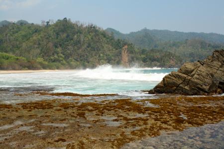 Pantai Pasir Putih Kiluan menyajikan pemandangan pantai dengan batu karang yang indah di pinggirnya