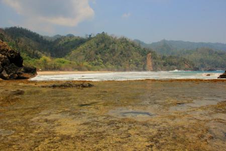 Pemandangan latar belakang bukit dengan terumbu karang menjadi paduan yang indah di pantai ini