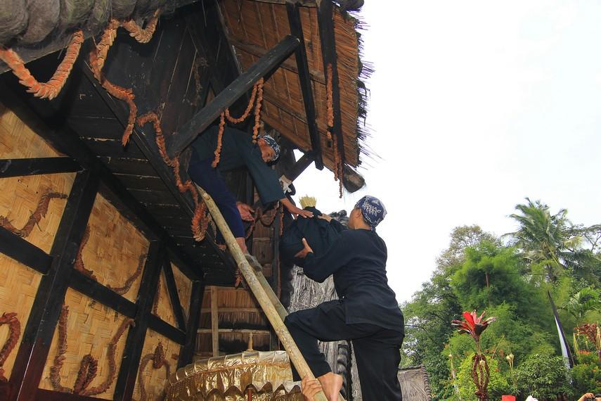 Proses memasukkan padi ke dalam lumbung dalam perayaan puncak Seren Taun di Kampung Budaya Sindang Barang