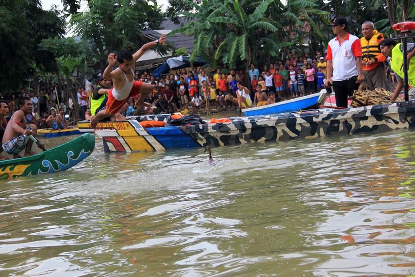 Seorang peserta melompat dari perahu untuk mendapatkan bebek yang dilepas dalam tradisi lempar bebek