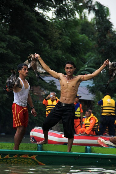 Seorang peserta lempar bebek yang berhasil mendapatkan bebek dalam tradisi lempar bebek Sungai Cisadane