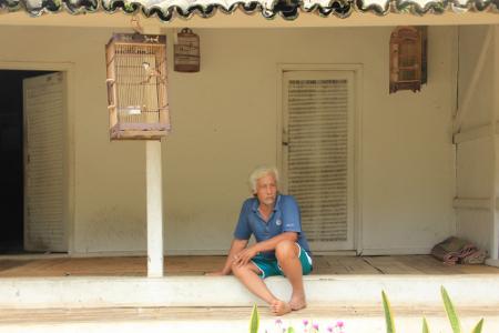 Salah satu warga di Pemukiman adat Kampung Pulo sedang duduk di depan teras rumahnya