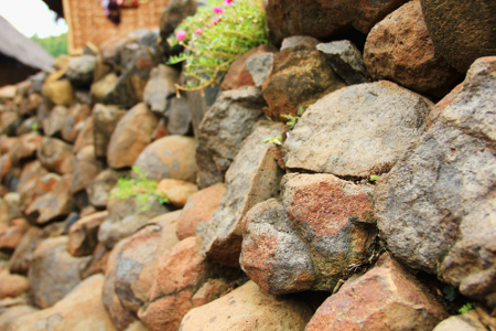 Tumpukan batu yang disusun menjadi dinding di sekitar lingkungan Kampung