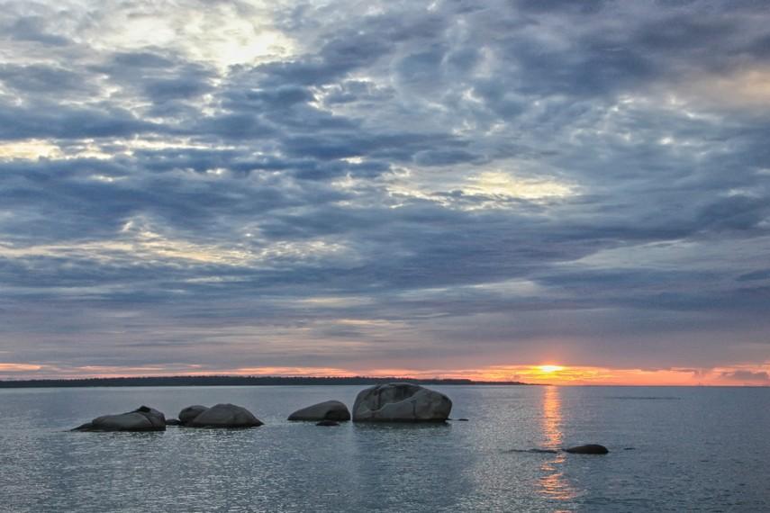 Duduk diatas batu granit sambil memandangi laut dan sunset menjadi hal yang tak terlupakan di pantai ini