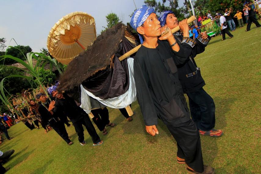 Menggunakan baju kampret, masyarakat mengarak berbagai dongdang menuju alun-alun Kampung Budaya Sindang Barang