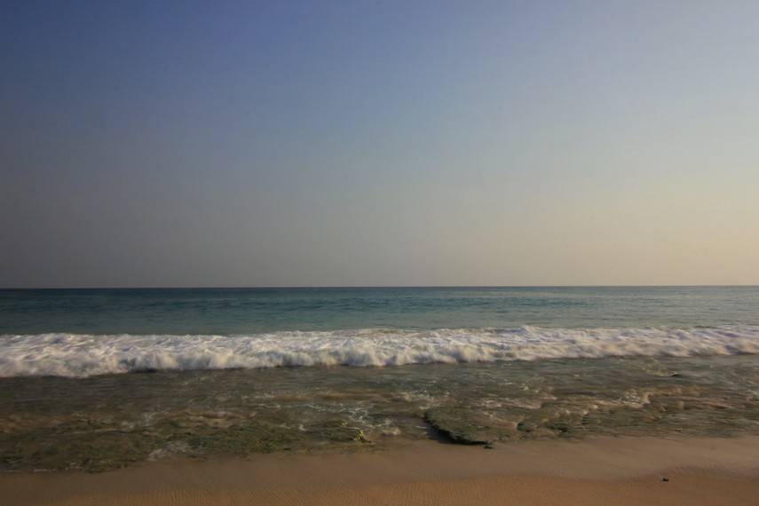 Hamparan pasir dengan kontur tepinya yang melengkung menjadi salah satu lanskap yang tersaji di pantai ini