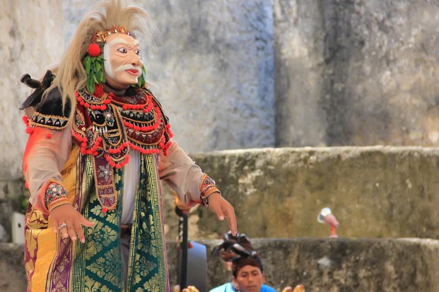 Seorang penari topeng tua menggunakan topeng dari kayu ylang-ylang dengan busana yang megah