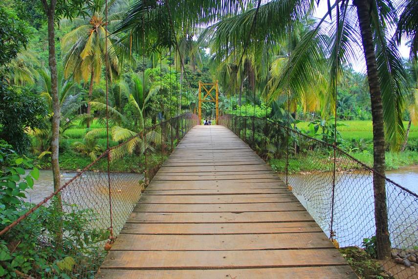 Pengunjung harus melewati pematang sawah, tepian sungai, hingga jembatan gantung sebelum sampai ke Gua Lalay
