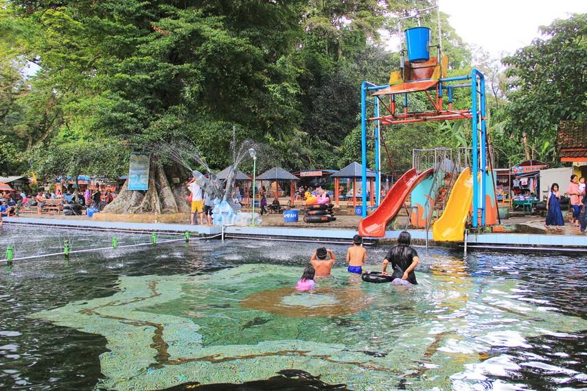 Pemandian Cibulan menggabungkan hiburan wahana bermain air dengan keberadaan mitos ikan dewa