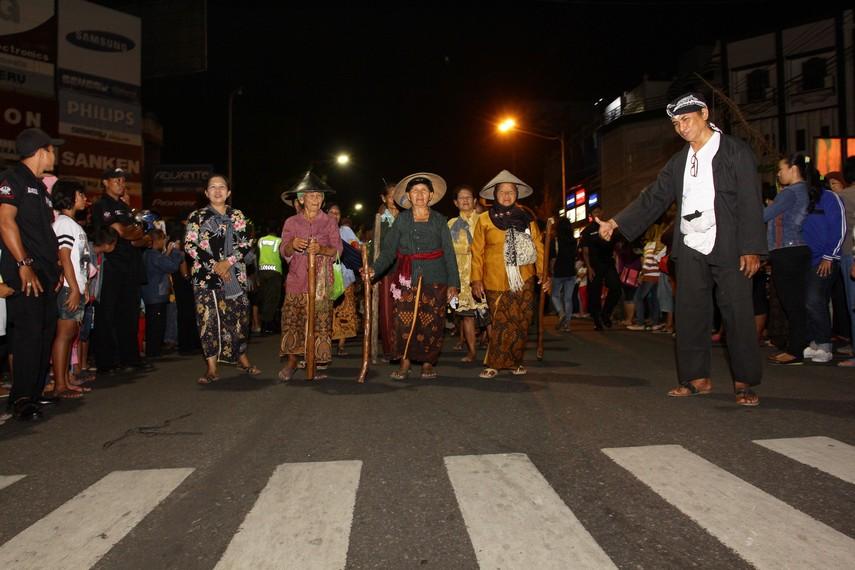 Sambil memegang alu atau alat penumbuk padi dan memakai topi caping ibu-ibu ini berjalan sepanjang jalan protokol di Kota Solo