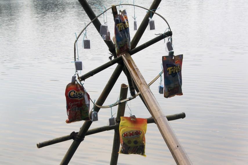 Berbagai hadiah digantungkan pada ujung batang pohon pinang