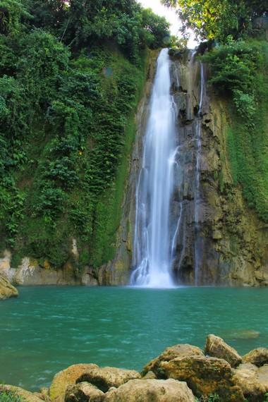 Air bewarna hijau kebiru-biruan dan disebelahnya terdapat air terjun yang dihiasi dengan dinding alami bebatuan yang besar