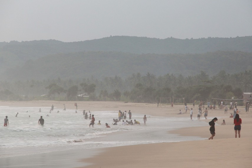 Gulungan ombak yang mengecil di bibir pantai menjadi permainan yang menyenangkan bagi sekelompok orang di pantai ini