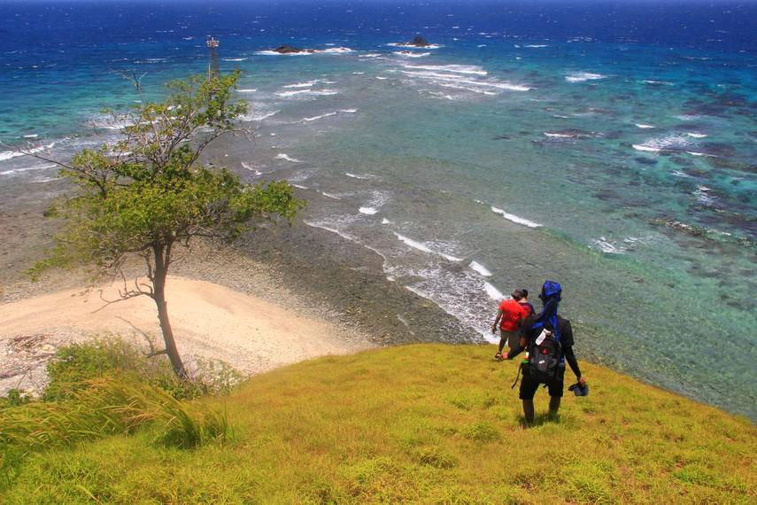 Perpaduan lautan yang biru, pulau dikejauhan dan gumpalan awan putih menjadi pemandangan yang tersaji dari atas pulau ini