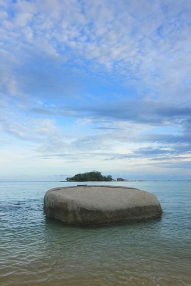 Paduan cantik pemandangan batu granit dan pulau di tengah laut dapat dilihat di Pantai Tanjung Kiras