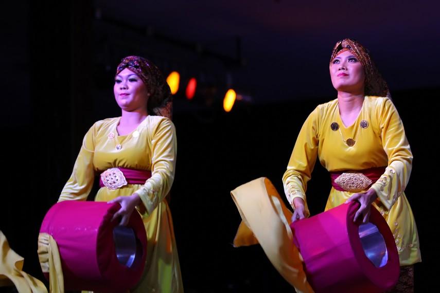 Penari yang semuanya perempuan mengenakan baju kurung berwarna cerah, bagian bawahnya dihiasi kain songket bermotif indah