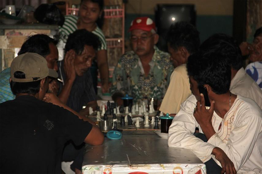 Selain mengobrol santai, sebagian warga juga menghabiskan waktu minum kopi sambil bermain catur