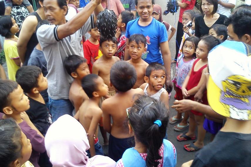 Anak-anak di sebuah perkampungan ikut memeriahkan HUT kemerdekaan RI dengan mengikuti lomba gigit duit