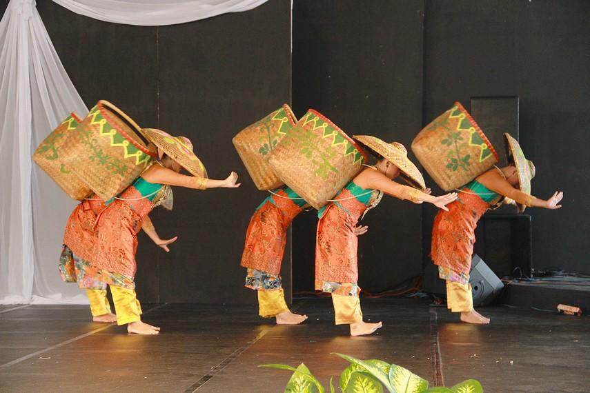 Di panggung, empat penari keluar dari dalam bakul dengan gerak perlahan para penari ini beranjak dari bakul dan mengenakan topi caping
