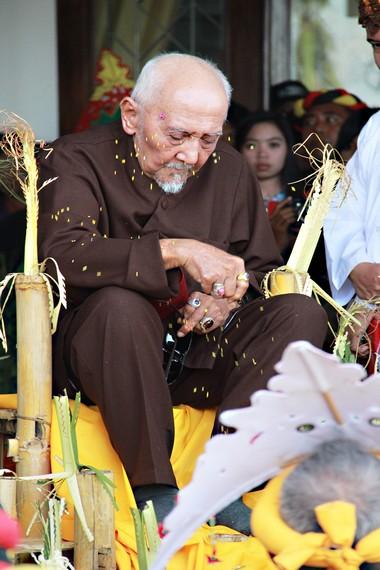Dewa menaburkan beras kuning ke arah Sultan pada prosesi tepong tawar