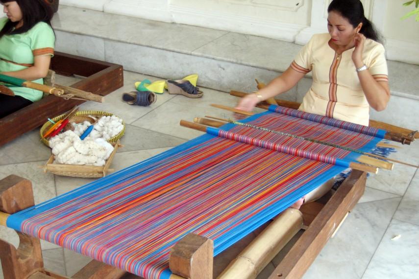 Benang-benang dengan warna cerah ditarik secara bergantian diantara bilah-bilah kayu