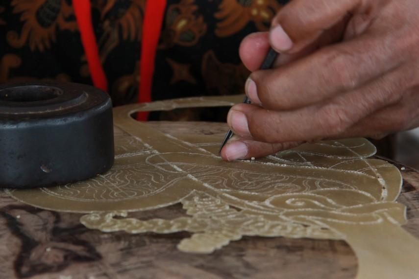 Tahap menatah dalam proses pembuatan wayang kulit dilakukan secara teliti untuk mendapatkan hasil yang sempurna