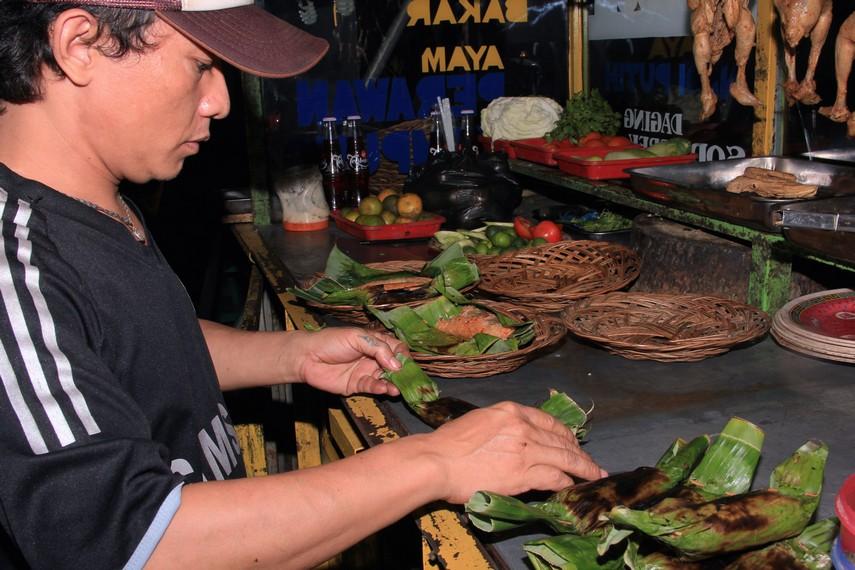 Nasi yang dibungkus daun pisang dan disajikan dengan lalapan membuat nasi bakar sumsum terasa nikmat