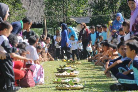Masyarakat Kampung Budaya Sindang Barang tengah bersiap untuk memperebutkan kue-kue yang sudah disediakan dalam ritual sedekah kue