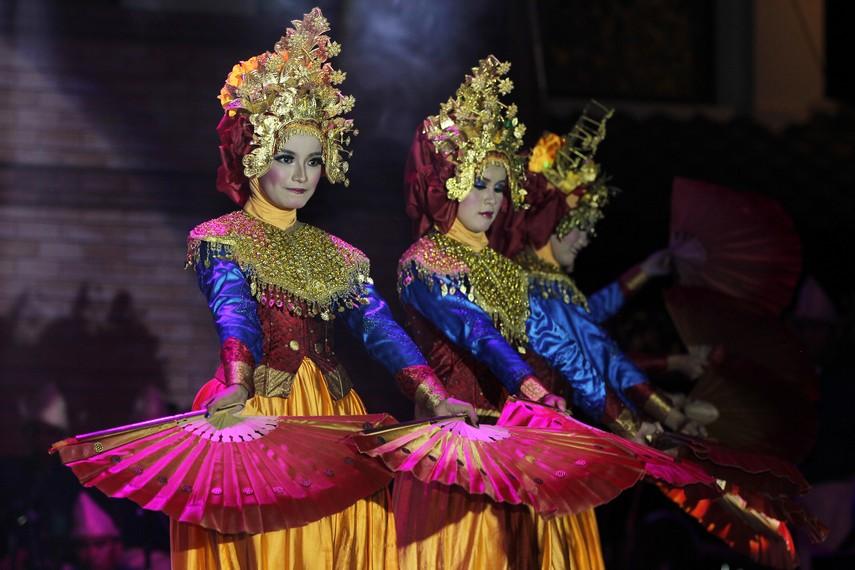 Penari kipas serumpun mengenakan baju kurung yang didominasi oleh warna keemasan sebagai ciri khas adat Sumatera Selatan