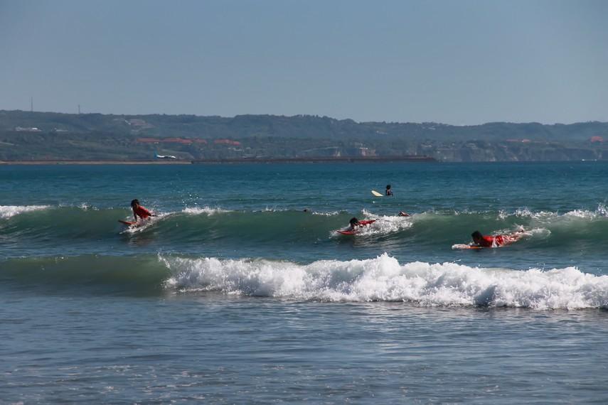 Pemandangan para peselancar yang berusaha menaklukkan ombak menjadi pemandangan yang sering dilihat di pantai ini