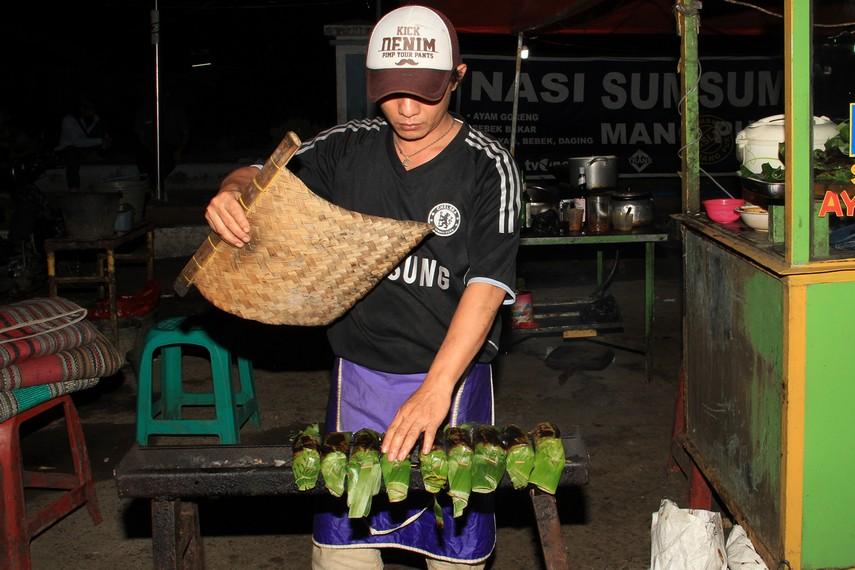 Seorang penjual nasi bakar sumsum sedang membakar nasi di atas panggangan