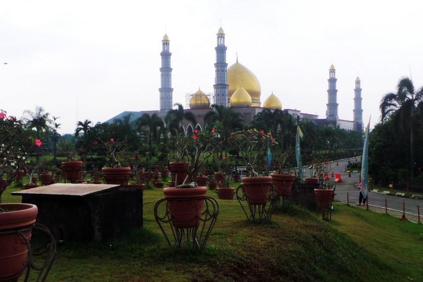 Memasuki area komplek Masjid Kubah Emas pengunjung akan melihat sebuah taman dengan pepohonan yang luas