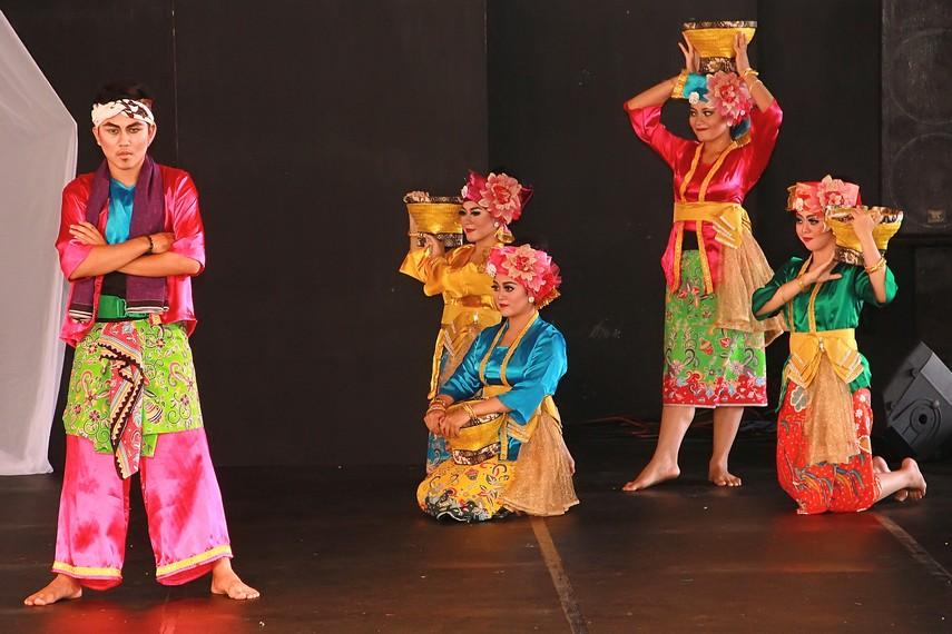 Para penari melakukan gerakan-gerakan seperti sedang menjalani kehidupan sehari-hari seperti penari wanita membawa bakul di pundak
