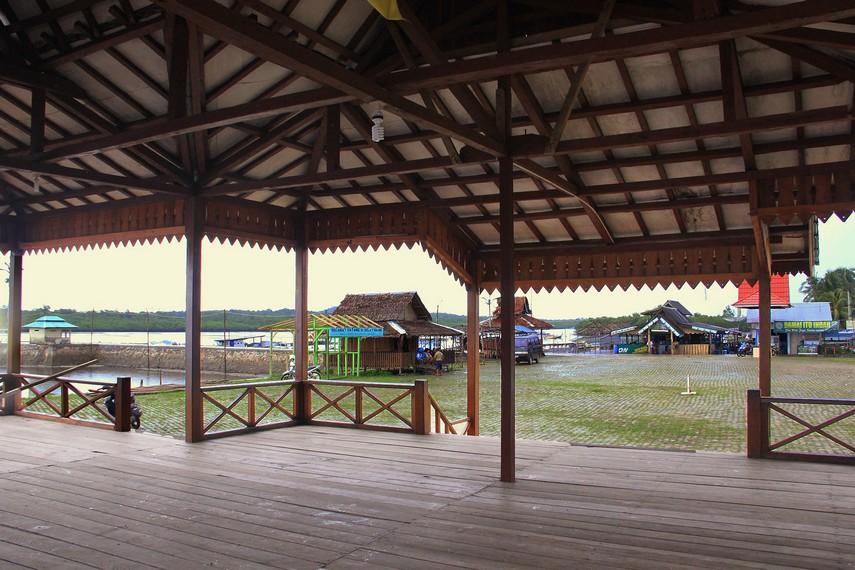 Selain pemandangan kapal nelayan, dari depan rumah adat ini juga dapat terlihat rumah-rumah penduduk di Selat Nasik