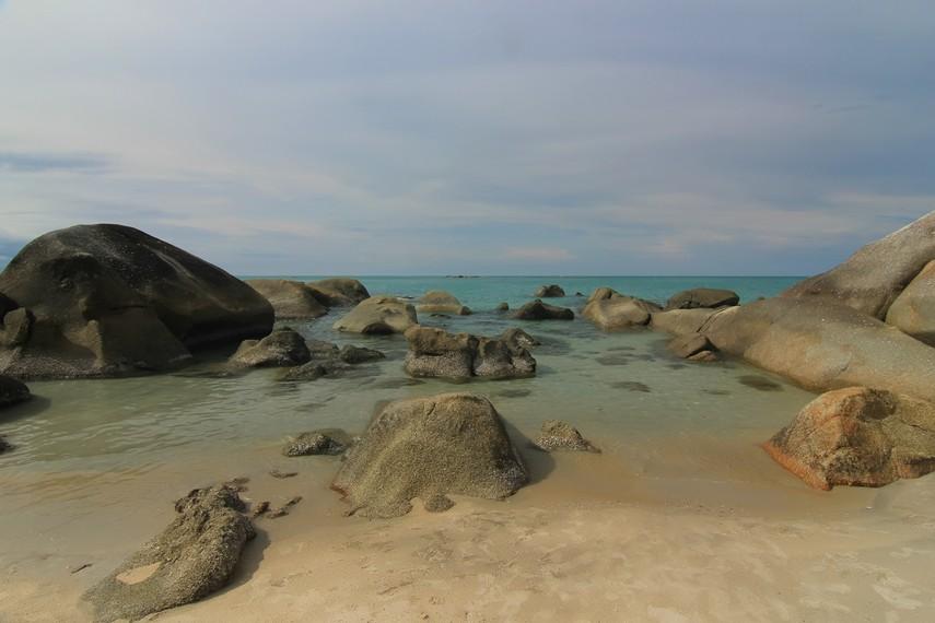 Keindahan Pantai Tanjung Pesona dihiasi dengan bebatuan granit dan air yang laut yang bewarna hijau