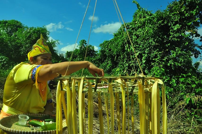 Dewa meletakkan nasi ragi di atas telasak gantung, sebagai bagian dari sesajian yang dipersiapkan dalam Menjamu Benua