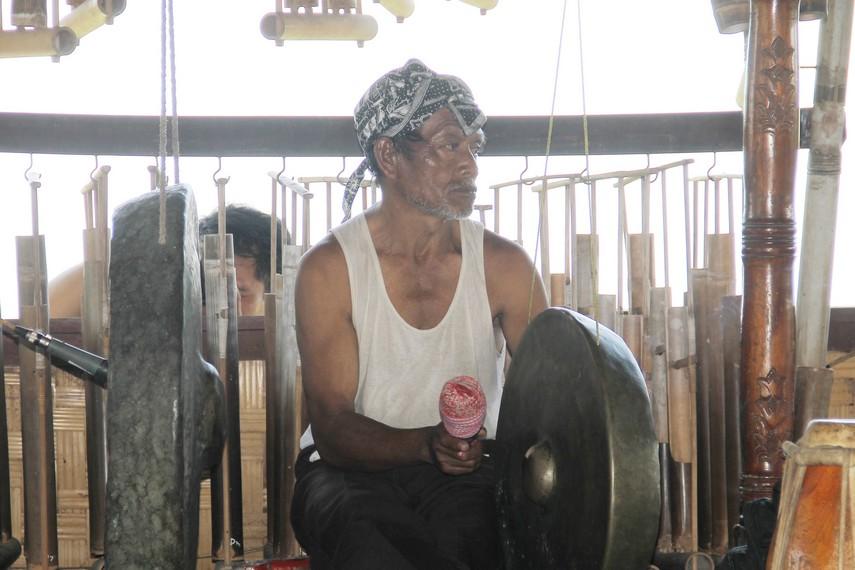 Salah seorang dari Kampung Budaya Sindang Barang sedang memainkan gong dan siyem dalam pementasan gamelan Sunda