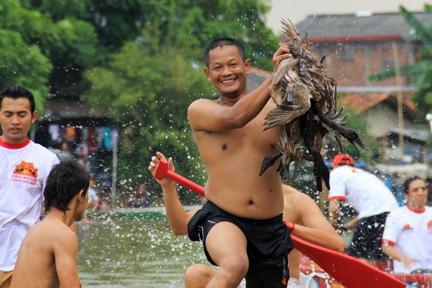 Kegembiraan seorang peserta yang berhasil menangkap bebek dalam tradisi lempar bebek di Sungai Cisadane