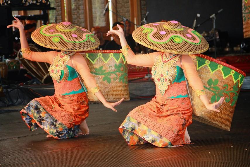 Para penari memakai topi caping hingga menutupi sebagian wajah seperti pemandangan yang kita lihat di perkebunan teh