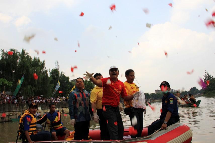 Pejabat walikota dan perwakilan dari perkumpulan Boen Tek Bio menabur bunga sebelum acara tradisi lempar bebek berlangsung