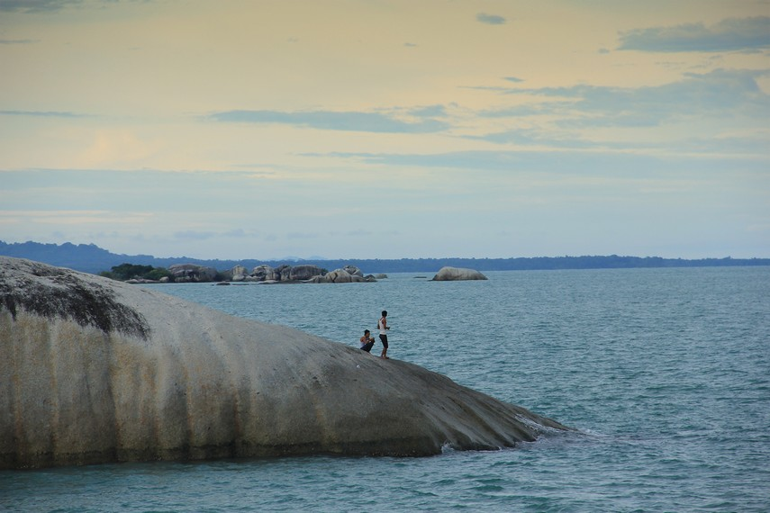 Berdiri di atas batu granit dan memandang laut lepas menjadi hal yang menyenangkan di Pantai Penyabong